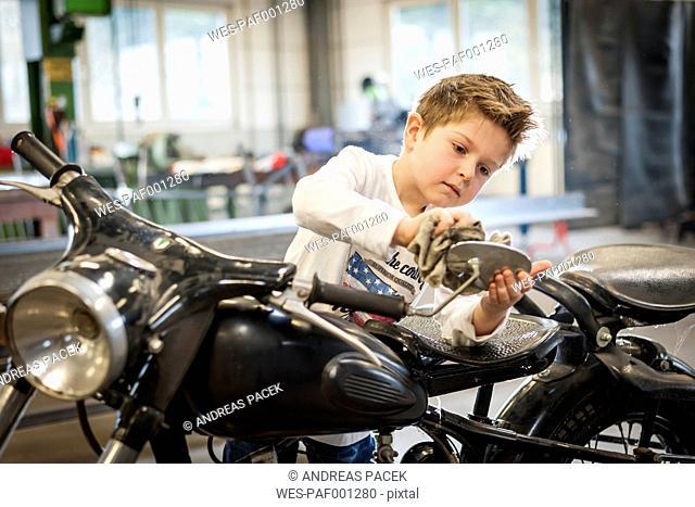 Boy polishing vintage moped