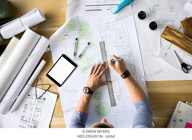 Overhead view architect drafting blueprints at table