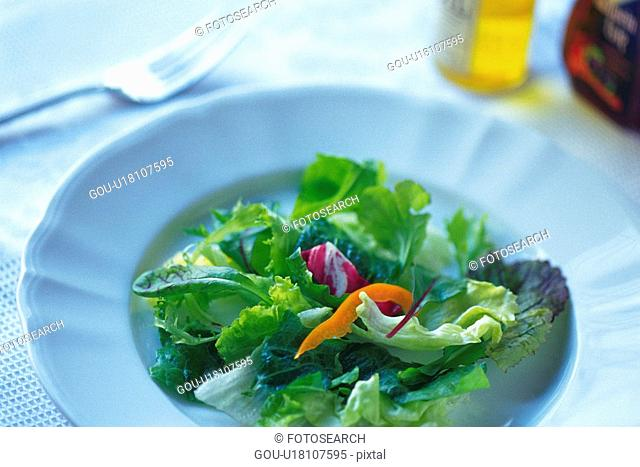 Mixed salad leaves on plate, two bottles and fork visible in background, Differential Focus