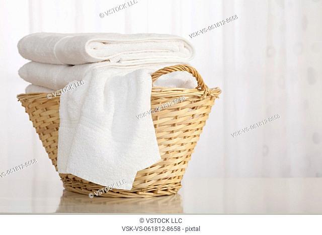 Studio shot of stack of white towels in Wicker Basket