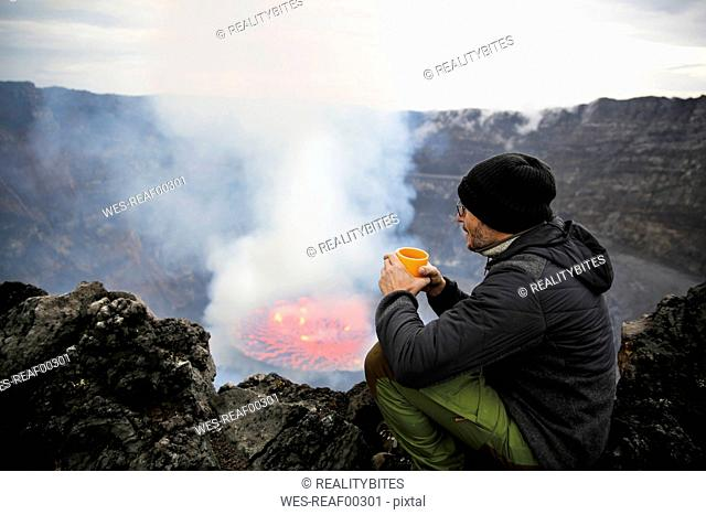 Africa, Democratic Republic of Congo, Virunga National Park, Man sittiing over Nyiragongo volcano crater
