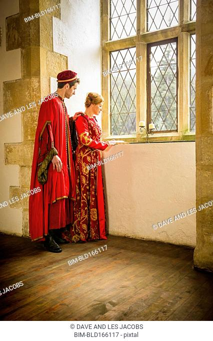 Caucasian couple in medieval costumes looking out castle window
