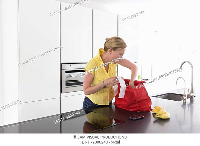 Mature woman unpacking groceries in modern kitchen