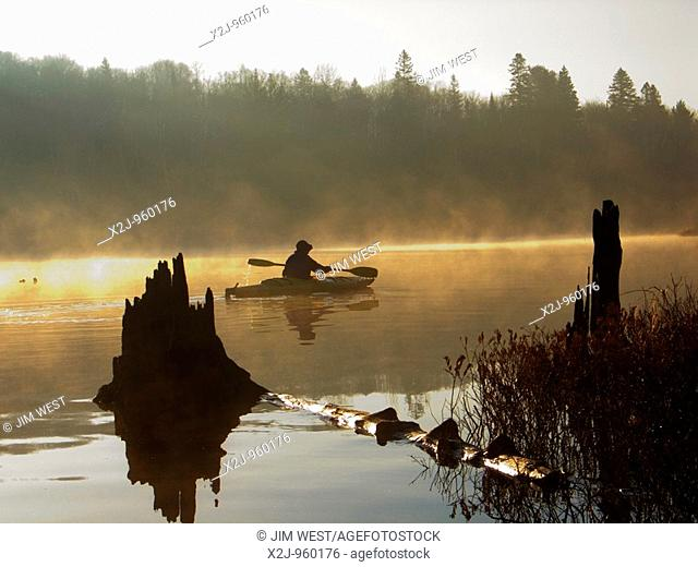 Algonquin Provincial Park, Ontario Canada - Gail Francis paddles a kayak on Tom Thomson Lake in the early morning while on a canoe/kayak camping trip in...