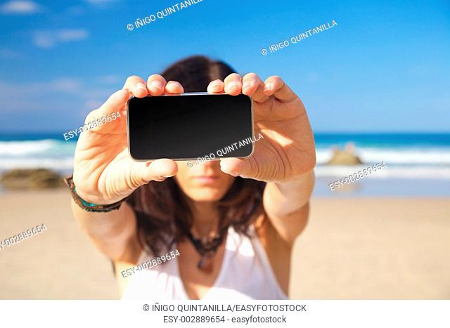 smart phone in woman hand on a beach in Asturias Spain