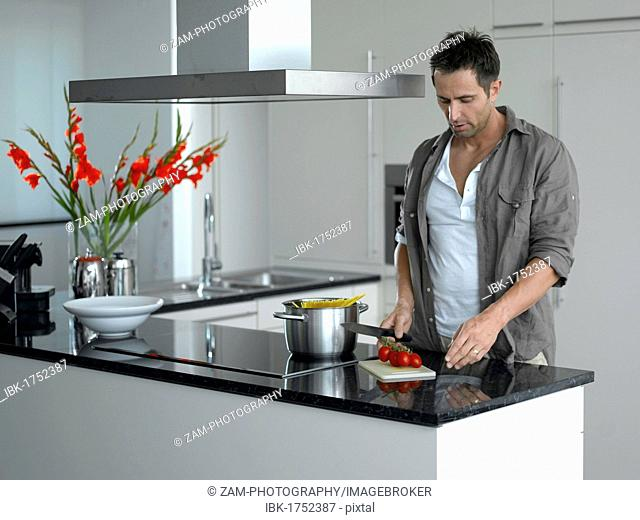 Man cutting tomatoes in a modern kitchen