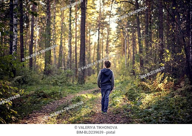 Caucasian boy wandering in forest