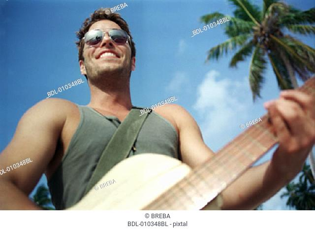 man on the beach playing his guitar