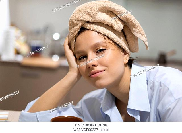 Portrait of smiling young woman with with hair wrapped in a towel in the kitchen