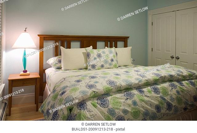 Bed in bedroom with blue and green comforter