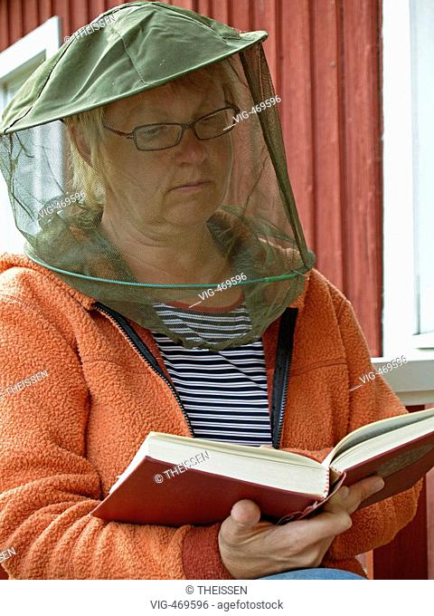 woman wearing a hat with gaze as protection against gnats mosquitos sitting in front of a red scandinavian timber wooden house reading a book