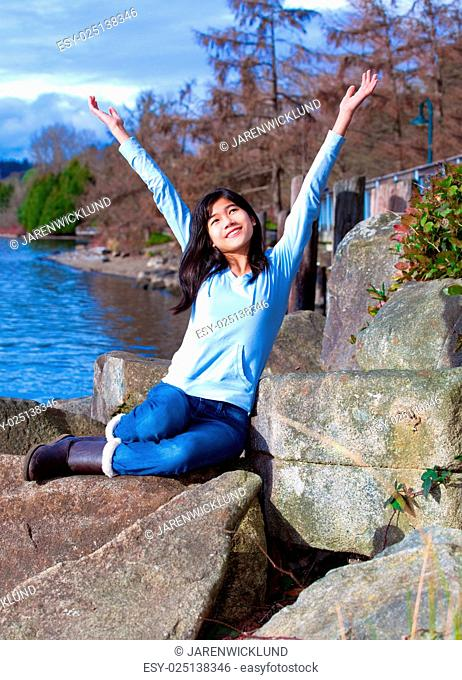 Young teen girl arms raised while sitting on large rock along la