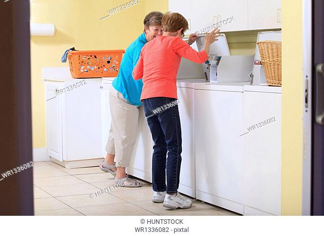 Senior women looking into washing machine in a laundry room