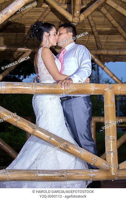 Wedding couple posing outdoors in a bamboo gazebo
