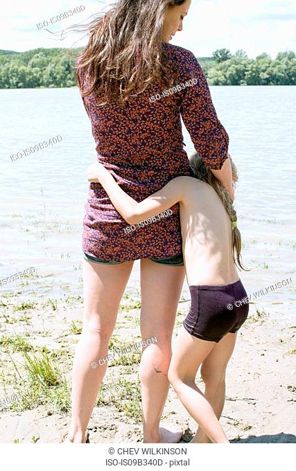 Rear view of woman and daughter at riverside