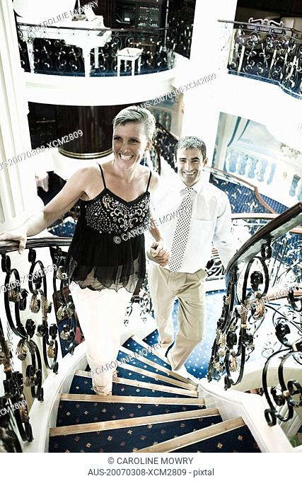 Mid adult couple moving up on a staircase of a cruise ship and smiling