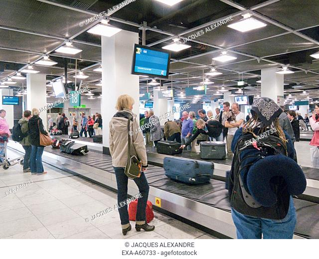 Passengers collecting luggage at an airport baggage collection
