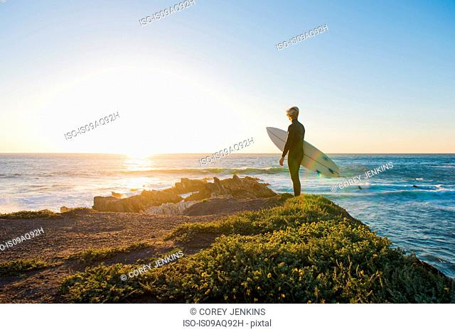 Young male surfer looking out to sea from clifftop at sunrise