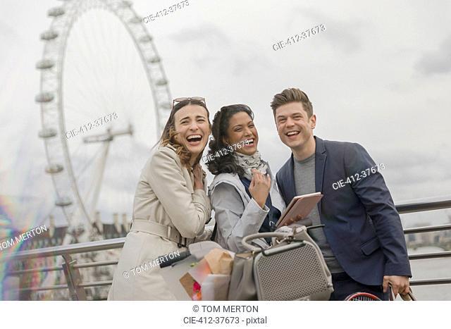 Portrait laughing friends with digital tablet near Millennium Wheel, London, UK