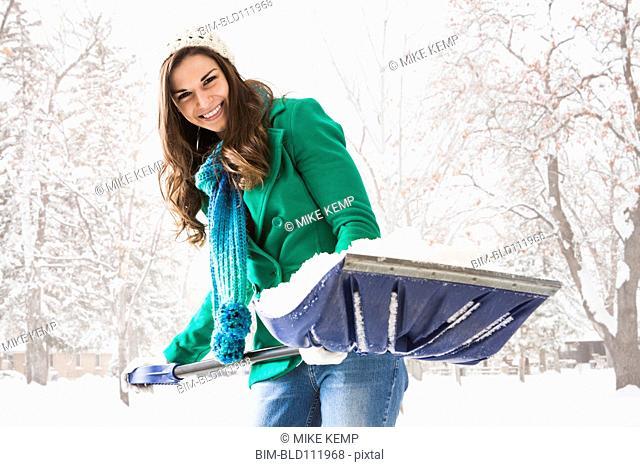 Caucasian woman shoveling snow outdoors