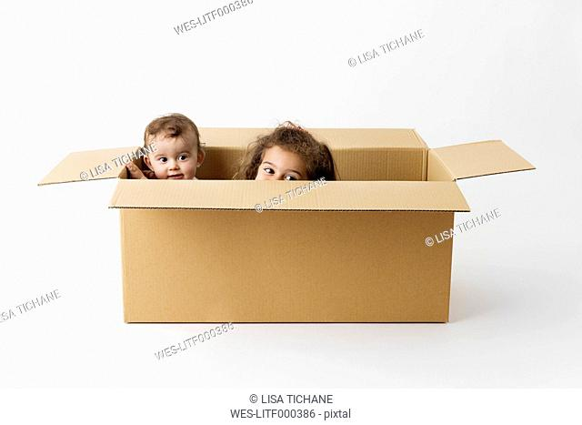 Two little children hiding together in a cardboard box