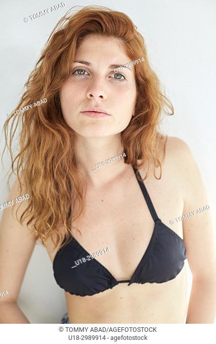 Half length portrait of young redhead woman wearing a black bikini, looking at camera