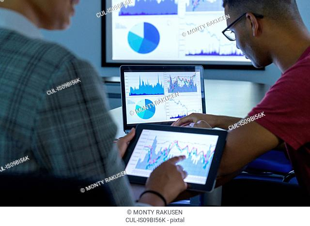 Businessman and woman using screens with graphs and charts in business meeting, close up