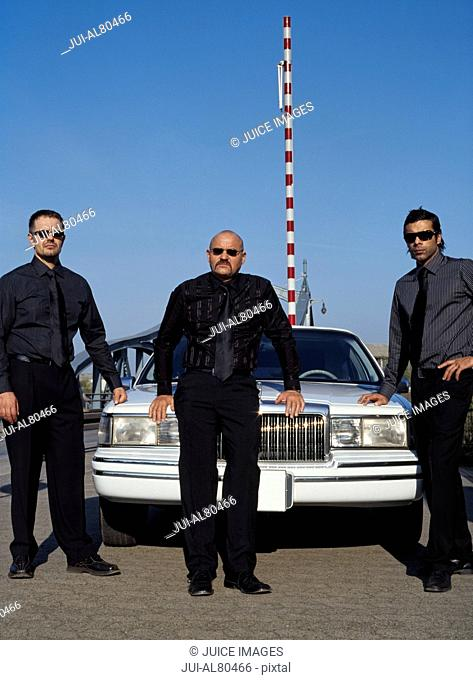 Three men dressed all in black at border crossing