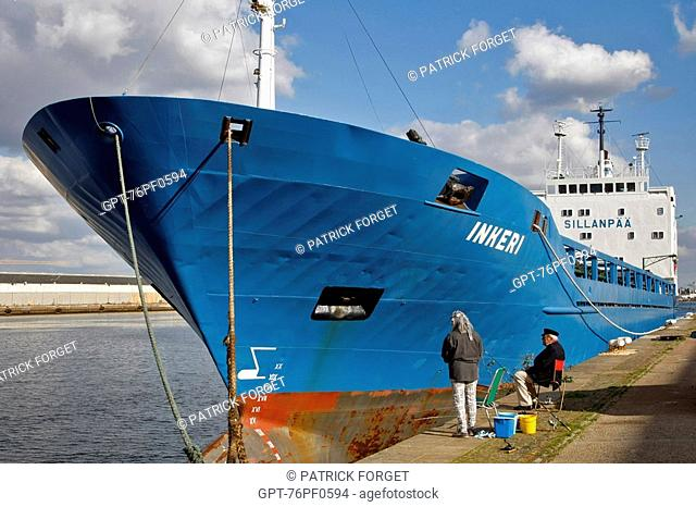 LINE FISHERMEN IN FRONT OF A DOCKED CARGO BOAT IN THE COMMERCIAL PORT, LE HAVRE, SEINE-MARITIME 76, NORMANDY, FRANCE