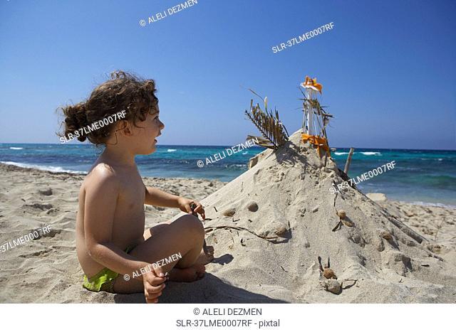 Girl building sandcastle on beach