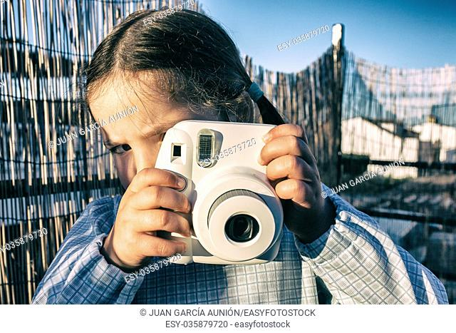 Cute little girl with instant picture photo camera. Vintage Filtered