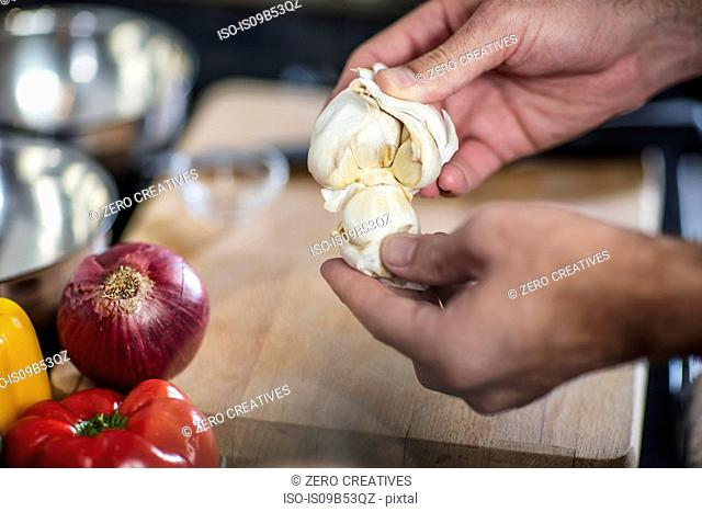 Chef peeling fresh garlic, close-up