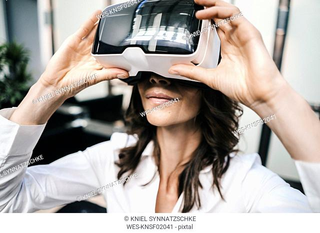 Businesswoman using VR goggles in office