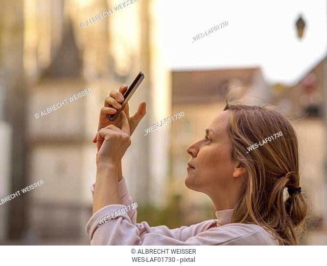 France, Chartres, young woman taking picture with smartphone in front of Notre-Dame de Chartres