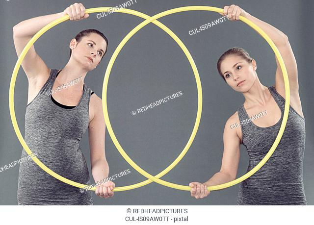 Young women practising with hula hoop, grey background