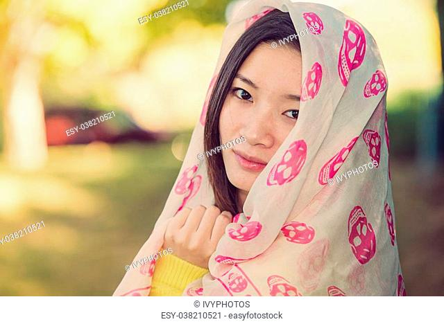 Beautiful young woman with skull covering head and face in sunshine