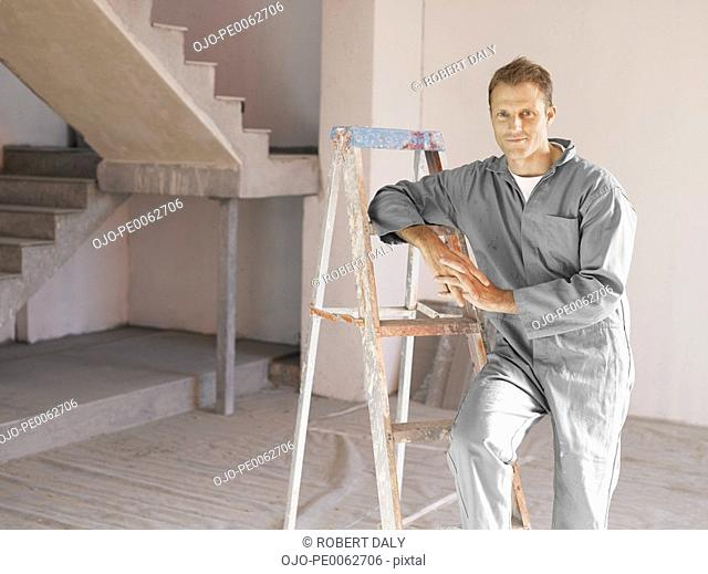 Painter posing with ladder in unfinished room