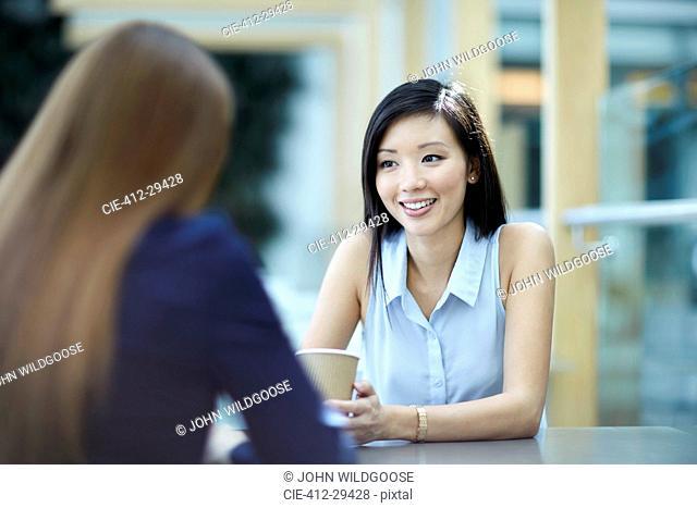 Smiling businesswomen talking on coffee break
