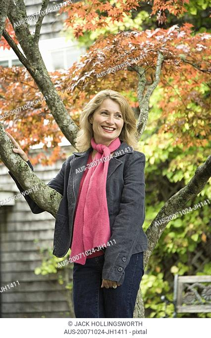 Mature woman leaning against a maple tree and smiling