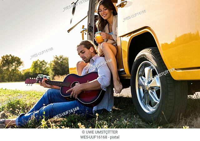 Affectionate couple on a road trip, taking a break, playing guitar
