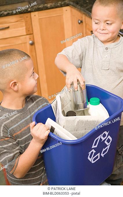 Hispanic brothers recycling