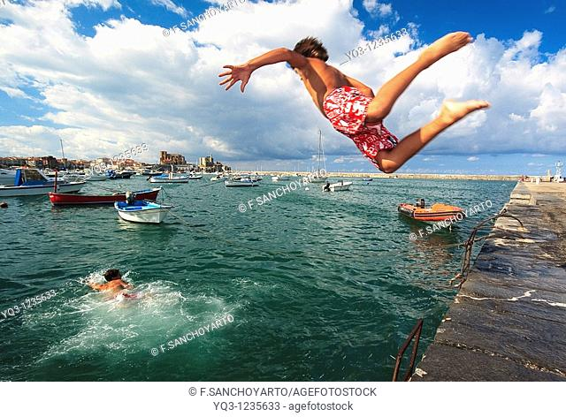 Children jumping in water at Muelle Don Luis. Castro Urdiales Bay, Cantabria, Spain
