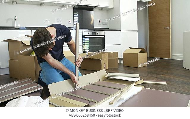 Man sitting on the floor and following furniture assembly instructions.Shot on Sony FS700 in PAL format at a frame rate of 25fps