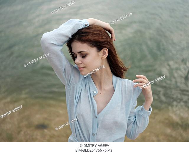Smiling Caucasian woman standing near ocean