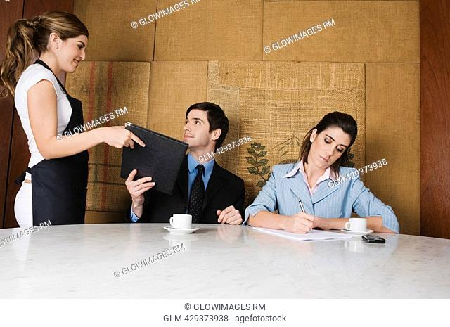 Waitress giving a menu to a businessman