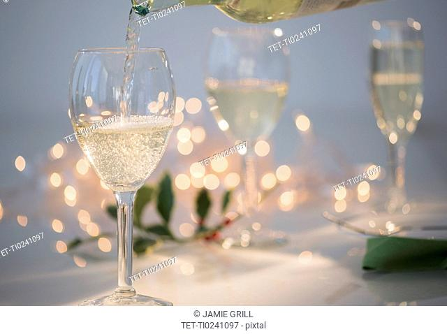 Pouring white wine into glasses