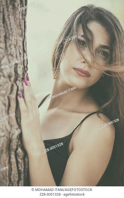 Beautiful young woman hair covering face looking away