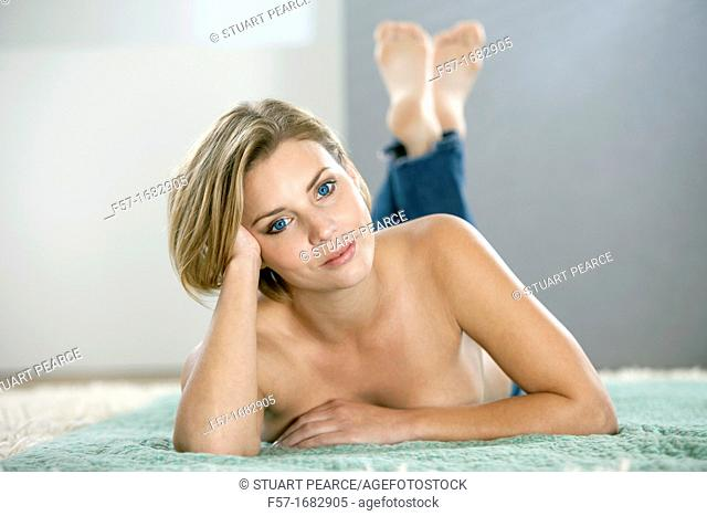 Naked young woman lying on a rug