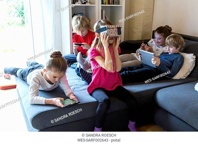 Five children on one couch using different digital devices