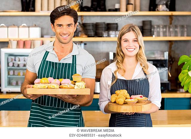 Portrait of waiter and waitress holding a tray of cupcakes